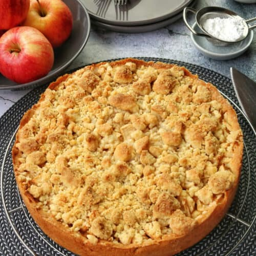 A whole apple cake with crumble topping. A bowl of Apples and plates in the background.